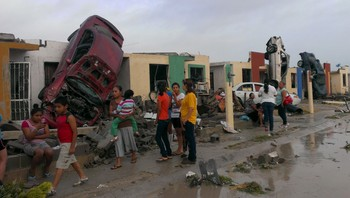 MEXICO-TORNADO/ Residents stand outside their homes as damaged cars are seen after a tornado hit the town of Ciudad Acuna