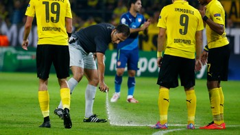 SOCCER-CHAMPIONS/ Referee Benquerenca uses vanishing spray to mark line on the pitch for Dortmund defenders to stand behind during Arsenal free-kick in Champions League soccer match against Arsenal in Dortmund - Det er denne sprayen Tysklands fotballforbund ikke tør å bruke lenger. - Foto: KAI PFAFFENBACH / Reuters