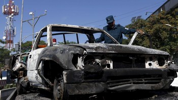 AFGHANISTAN-ATTACK-TALIBAN Afghan policeman inspects the wreckage of a car after Taliban attack on a guesthouse in Kabul