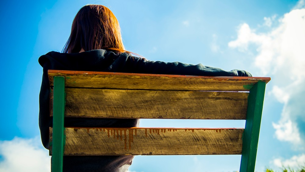Backside of Woman sit on wooden chair with blue sky1