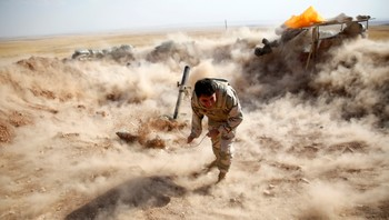 IRAQ-CRISIS/ A Kurdish Peshmerga fighter launches mortar shells towards Zummar, controlled by Islamic State, near Mosul - En kurdisk Peshmerga-soldat avfyrer en mortergranat mot den islamske statens styrker i kamper nær Mosul. - Foto: AHMED JADALLAH / Reuters