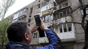 UKRAINE-CRISIS/ An employee of the Organisation for Security and Cooperation in Europe (OSCE) takes pictures of a residential building, which according to locals was recently damaged by shelling, in Donetsk