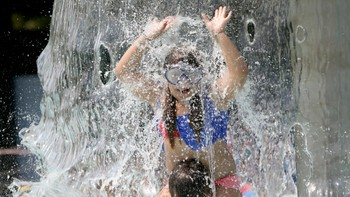 GERMANY-WEATHER/ A girl plays in the waterfall at the the fun bath in Endenich