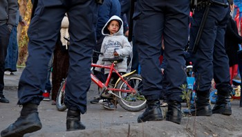 FRANCE/ A Roma child looks at French police standing guard as Roma families are evicted from their illegal camp near the Var river in Nice