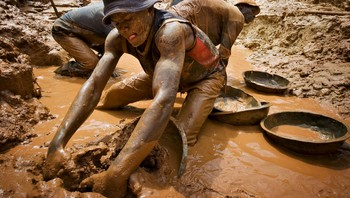 EU-MINERALS/CONFLICT File photo of a gold miner scooping mud while digging an open pit at the Chudja mine in the Kilomoto concession near the village of Kobu