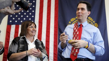 USA-ELECTION/ Potential Republican 2016 presidential candidate Wisconsin Governor Walker autographs plastic potatoes next to his wife Tonette after speaking to local activists and elected officials in Derry