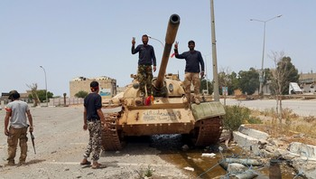 LIBYA-POLITICS/ Members of the Libyan pro-government forces gesture as they stand on a tank in Benghazi