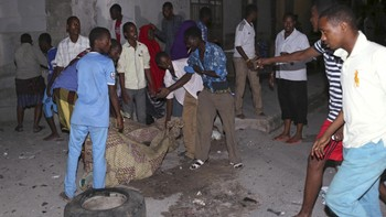 SOMALIA-ATTACKS/ Residents carry the dead body of a man who was killed in an explosion at the gate of Wehliya Hotel hotel in Mogadishu