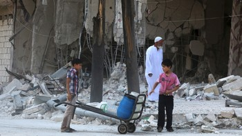 MIDEAST-CRISIS/SYRIA Children stand near a damaged building from what activists said was barrel bombs dropped by forces loyal to Syria's President Al-Assad in Aleppo's eastern district of Tariq al-Bab