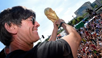 GERMANY/ German national soccer team coach Loew displays the World Cup trophy to supporters during celebrations in Berlin - Foto: POOL / Reuters