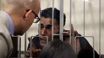 EUROPE-MIGRANTS/ Mohammed Ali Malek speaks with his lawyer Massimo Ferrante at the Catania's tribunal