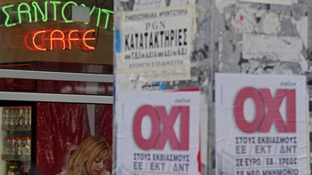 EUROZONE-GREECE/ The word 'No' in Greek is seen on posters sticked on a wall as a woman is seen at a cafe in Athens