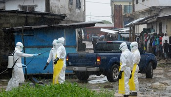 HEALTH-EBOLA/LIBERIA Health workers wearing protective clothing disinfect themselves after an abandoned dead body presenting with Ebola symptoms was found at Duwala market in Monrovia - Helsearbeidere forbereder seg på å undersøke et lik med ebolasymptomer i Monrovia. - Foto: STRINGER / Reuters