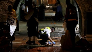 ISRAEL-PALESTINIANS/ A member of the Zaka Rescue and Recovery team cleans blood stains at the scene where a Palestinian was shot dead after he stabbed and killed two people in Jerusalem's Old City