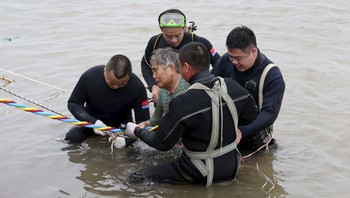 CHINA-SHIP/ A woman is helped after being pulled out by divers from a sunken ship in Jianli
