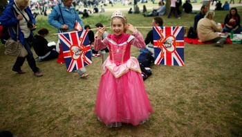 BRITAIN-WEDDING/ A girl wearing a costume plays with flags bearing the images of Britain's William, Duke of Cambridge and Catherine, Duchess of Cambridge, at St James Park in central London