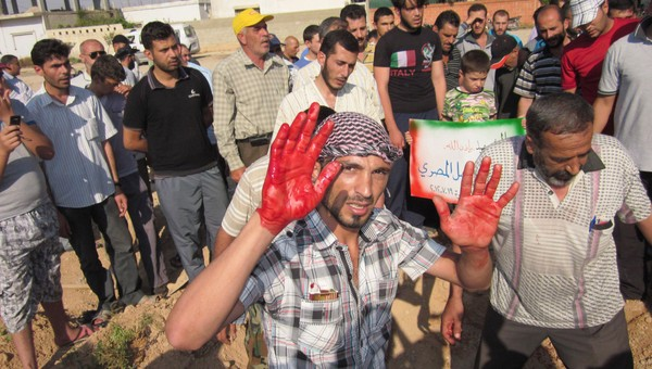 SYRIA-CRISIS/ A man holds up blood-stained hands, from the blood of Faisal Al-Masri, during his funeral at Qusseer neighbourhood of Homs - Ein mann held opp sine blodige hender under ei gravferd - Foto: HANDOUT / Reuters