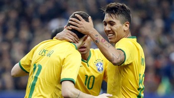 SOCCER-FRIENDLY/FRANCE-BRAZIL Brazil's Oscar celebrates with team mates Neymar and Firmino after scoring against France during their international friendly soccer match at the Stade de France