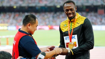 ATHLETICS-WORLD/ Usain Bolt of Jamaica, gold medalist, receives a present Song Tao, a cameraman of CCTV, after the podium ceremony for the men's 200 metres event during the 15th IAAF World Championships at the National Stadium in Beijing