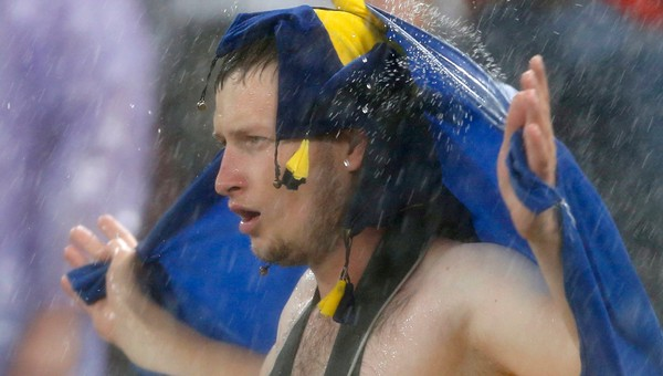 SOCCER-EURO/ Ukrainian fan stands in the rain after their Group D Euro 2012 soccer match against France was suspended at the Donbass Arena in Donetsk - Fansen holdt ut i regnværet mens de ventet på at kampen skulle starte igjen. - Foto: ALESSANDRO BIANCHI / Reuters