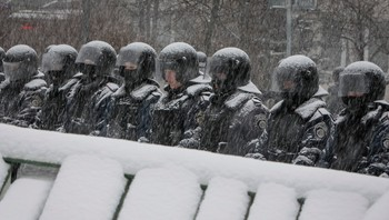 UKRAINE/ Interior ministry personnel stand guard during snowfall on a street in Kiev - Foto: GLEB GARANICH / Reuters