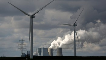 GERMANY/ Wind turbines are seen in front of a coal power plant of German utility RWE Power near the western town of Neurath