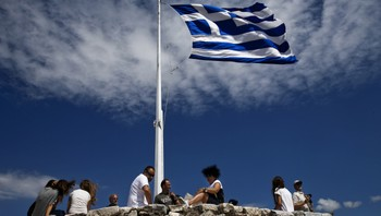 EUROZONE-GREECE/TOURISTS People sit under a Greek national flag atop the Acropolis hill archaeological site in Athens