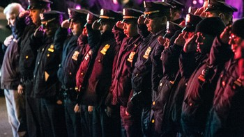 USA-NEWYORK/POLICE Police officers line the route as vehicles containing the bodies of the two New York Police officers who were shot dead drive by in the Brooklyn borough of New York - Foto: STEPHANIE KEITH / Reuters