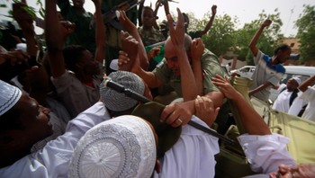 People cheer with soldiers during a celebration march in Khartoum