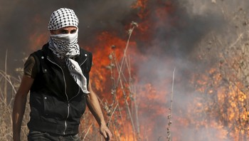 PALESTINIANS-ISRAEL/GAZA Masked Palestinian protester walks in front of a fire during clashes with Israeli troops near the Israeli border fence in northeast Gaza