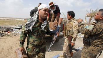 MIDEAST-CRISIS/IRAQ TIKRIT Members of Iraqi security forces carry bombs that were buried in the ground by Islamic State militants in Tikrit