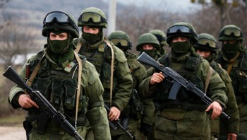 UKRAINE-CRISIS/ Armed men, believed to be Russian servicemen, march outside an Ukrainian military base in the village of Perevalnoye