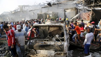 MIDEAST-CRISIS/IRAQ-VIOLENCE Residents gather at the site of a truck bomb attack at a crowded market in Baghdad