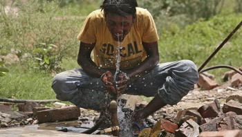 INDIA-HEATWAVE/ A worker washes his face at the construction site of a commercial complex on a hot summer day in Amritsar