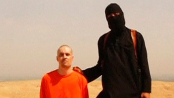 SYRIA-CRISIS/BEHEADING Still image from undated video of a masked Islamic State militant holding a knife speaking next to man purported to be James Foley at an unknown location - Foto: REUTERS TV / Reuters