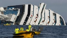 Oil recovery workers pass the Costa Concordia cruise (Foto: PAUL HANNA/Reuters)