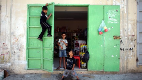 Israel abbas palestinian children play outside a shop in jenin