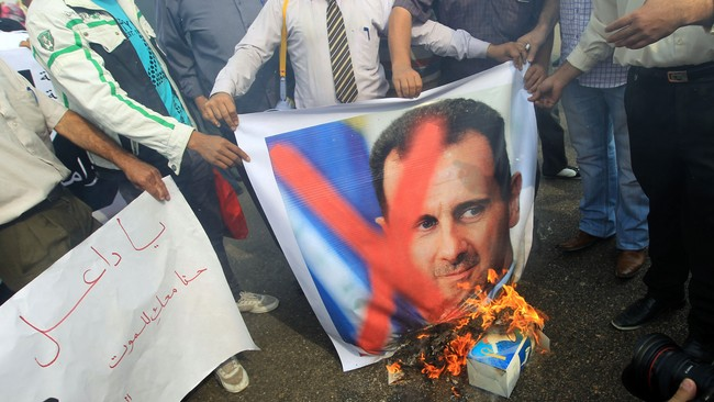 Demonstranter brenner portrettbilder av Assad (Foto: KHALED DESOUKI/Afp)