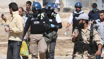 NOBEL-PEACE/OPCW File photo of U.N. chemical weapons experts wearing gas masks carrying samples collected from one of the sites of an alleged chemical weapons attack while escorted by Free Syrian Army fighters in the Ain Tarma neighbourhood of Damascus