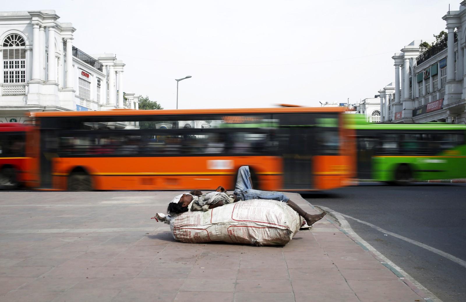 En mann tar en seg hvil på en sekk ved et travelt trafikkryss i New Delhi.
