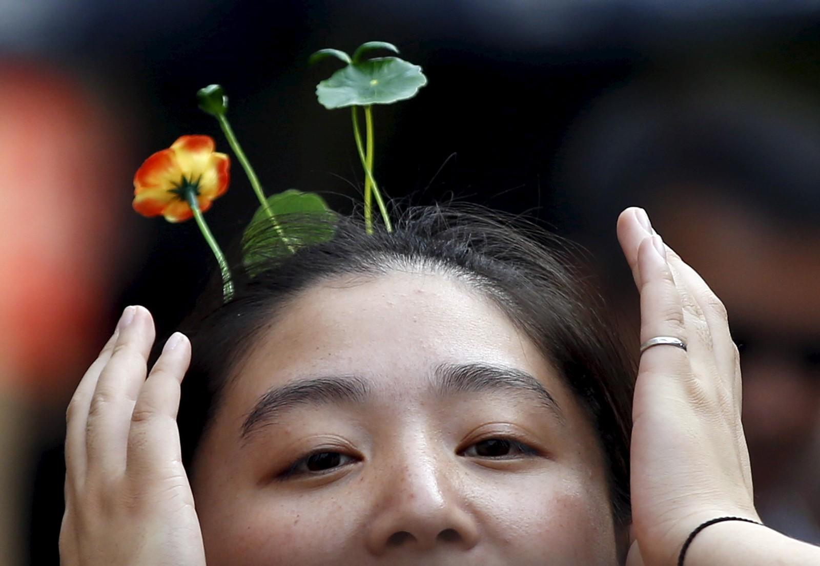 En kvinne med iøynefallende hårnåler fotografert mens hun vandret langs Nanluoguxiang-gaten i Beijing. Antenne-formede hårnåler har blitt en stor trend i den kinesiske hovedstaden, ifølge nyhetsbyrået Reuters.