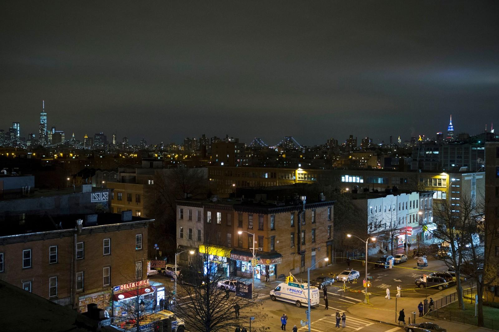 Manhattan skyline ses i bakgrunnen der etterforskere undersøker stedet der to politimenn ble skutt og drept.