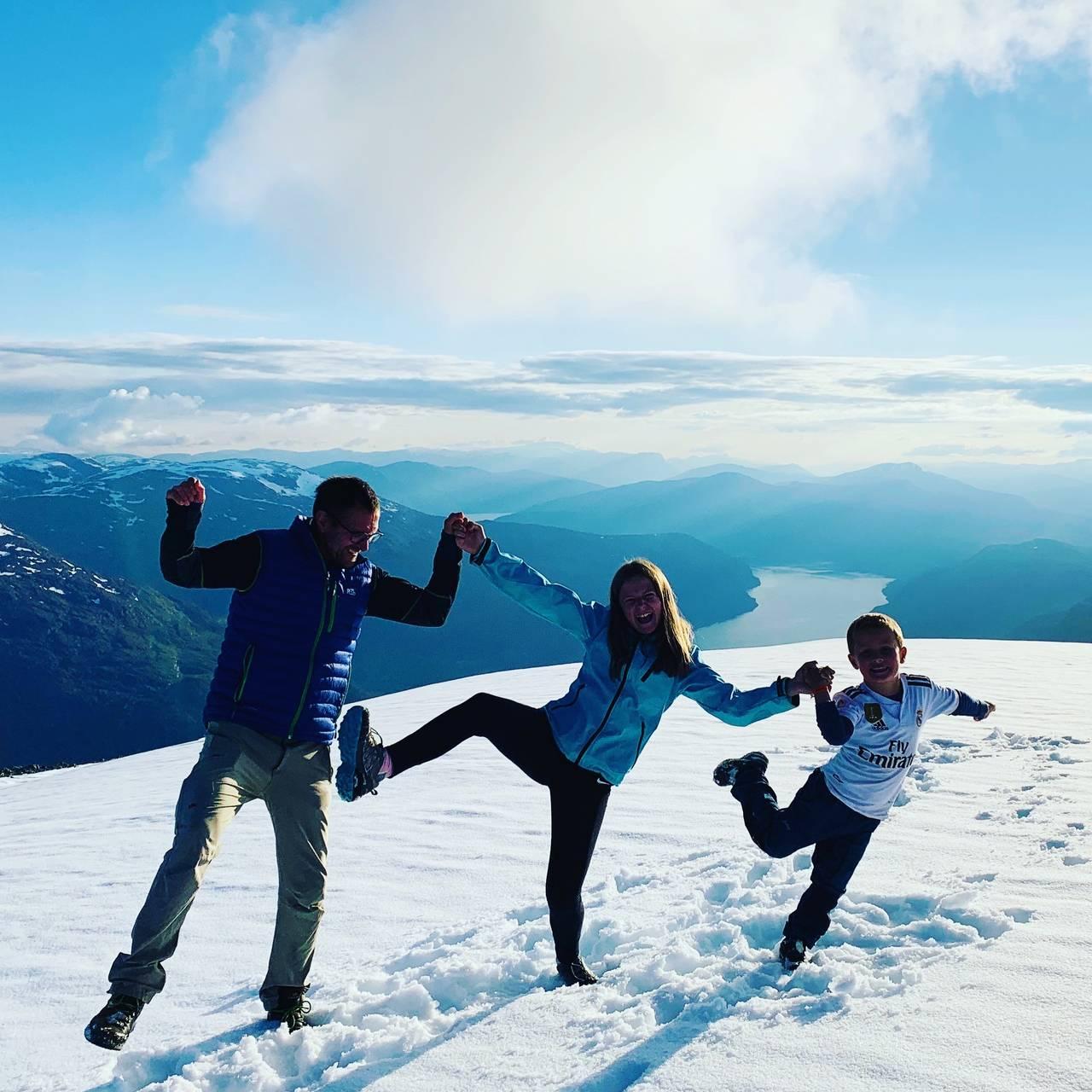 En familie danser på toppen av Skåla.
