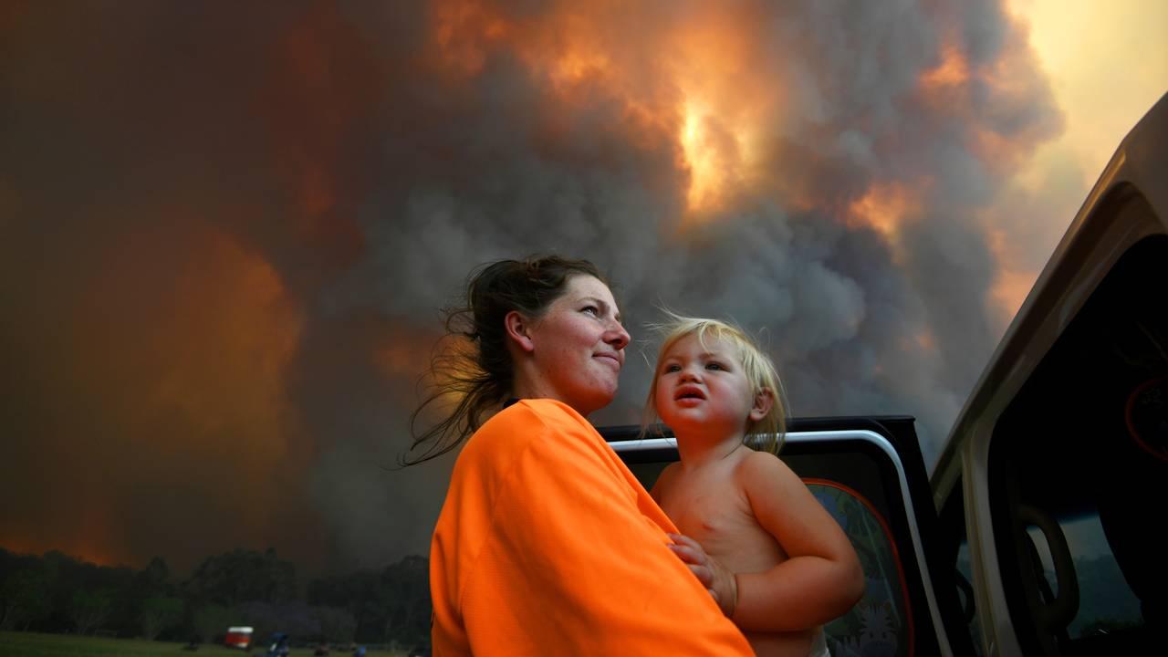 Sharnie Moren og hennes 18 måneder gamle datter Charlotte ser på mens røyken stiger opp nær Coffs Harbour tidligere denne uken.