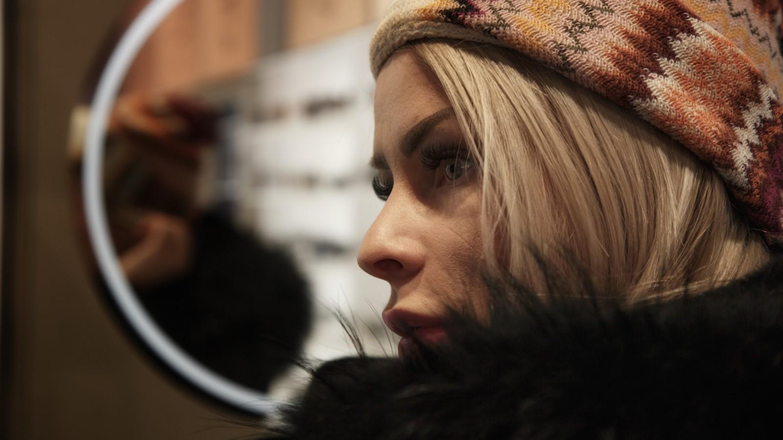 Nærbilde av en ung kvinne, ikledd topplue og jakke med pels, og hvor man tydelig ser kvinnens øyenvipper og opptegnede øyenbryn.