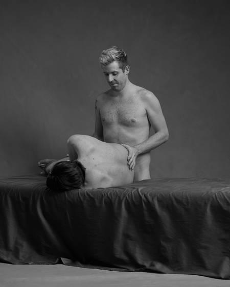 En naken mann ligger sidelengs på senga med en annen naken mann stående bak ham inntil rumpa hans