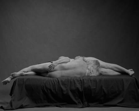 Et eldre par ligger på siden med hodet mot hverandres kjønnsorgan på en svart seng. Begge er nakne. Mannen har hvitt hår og ligger med ryggen mot kamera. Kvinnen har mørkt hår og holder på mannens rumpe. De simulerer oral sex.