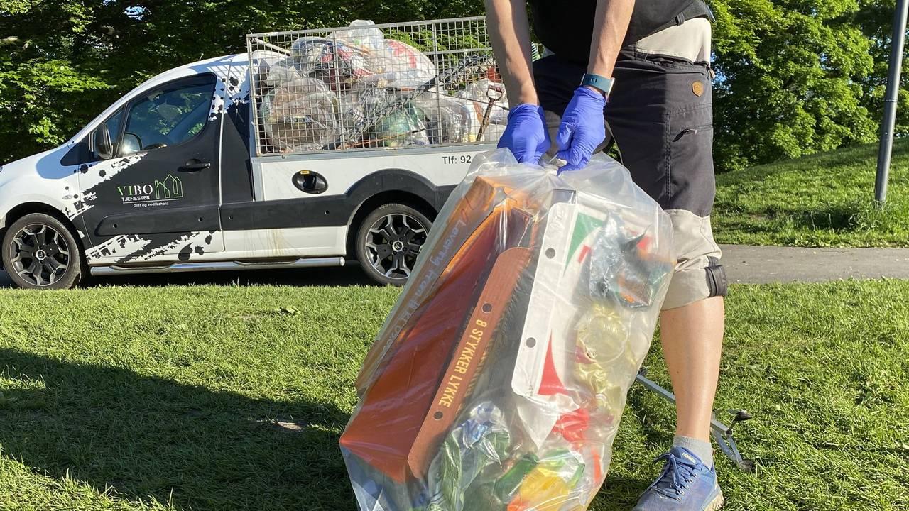 En person knyter sammen en sekk med søppel i parken på Sankthaugen