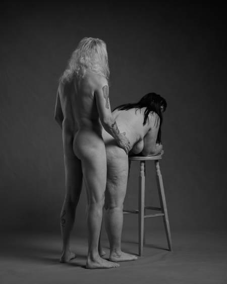 En naken dame med langt mørkt hår lener overkroppen over en høy krakk mens en naken mann med hvitt hår og tatoveringer står bak henne og holder henne på hoftene. De er et godt voksent par.
