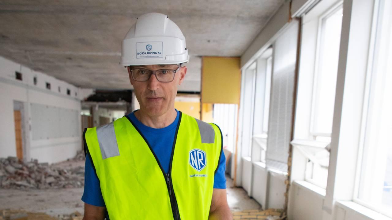Svein Egil Dagsland viser frem mursteinen som skal brukes om igjen. På bakken rundt han ligger det strødd murstein. Han har på refleksvest og vernehjelm.